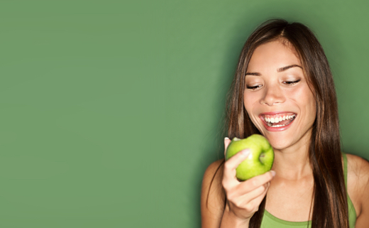 Girl with smile on her face is eating an apple