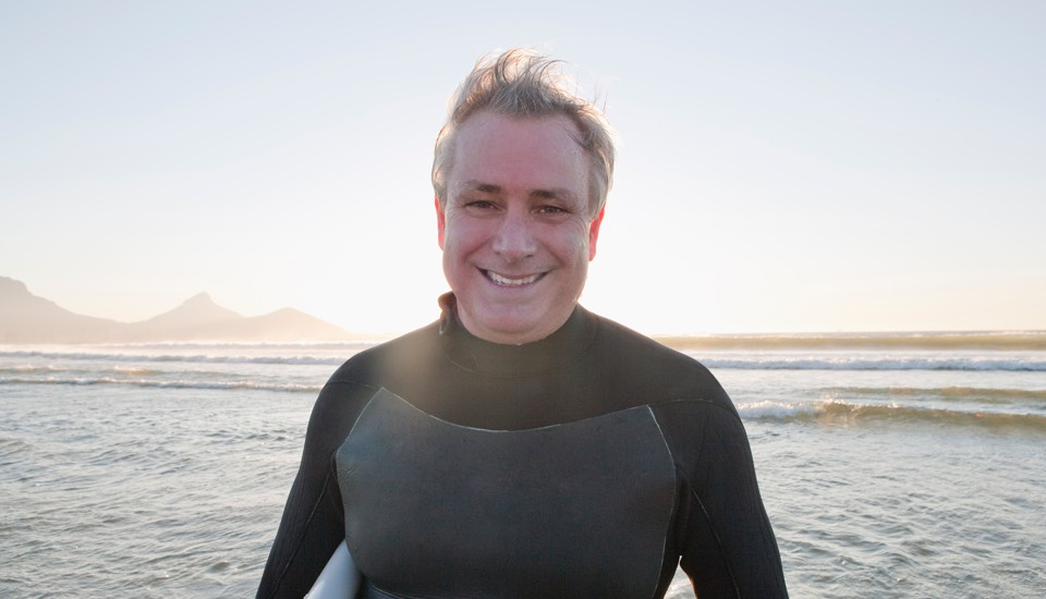 Portrait of a smiling man in a wet-suite standing on the ocean. Wind is blowing his hairs.
